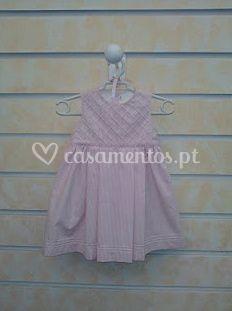 Vestido em pique cor de rosa com peitilho enviesado.