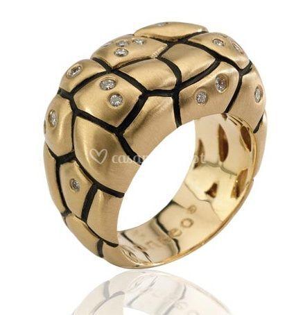 Anel dourado com detalhes irregulares em preto